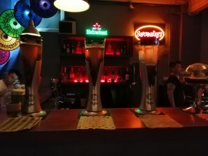 4 beer towers on bar signs behind